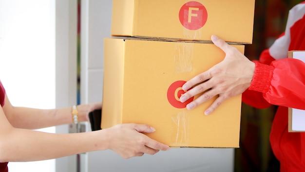 Les mains d'un coursier en uniforme de veste rouge livrent des colis à une cliente asiatique à la maison. livraison et expédition de colis, concept d'entreprise de commerce électronique porte à porte.