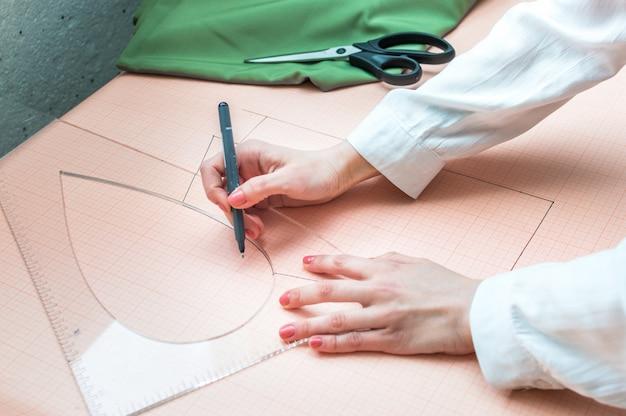 Les mains de couturière bouchent la conception de vêtements