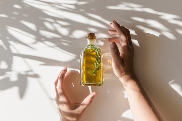 Mains couvrant la bouteille d'huile d'olive fraîche avec une brindille