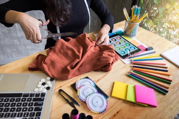 Mains cran de tailleur tailleur tailleur de tissu coupant un morceau de tissu