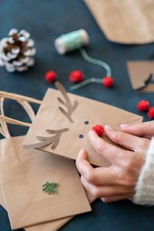 Mains créant un sac-cadeau de noël décoré de renne adorable