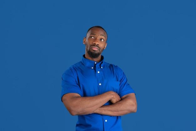 Les mains croisées. portrait monochrome de jeune homme afro-américain isolé sur le mur bleu du studio.