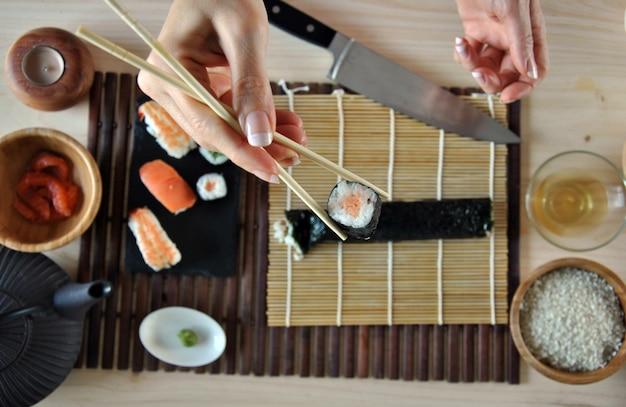 Mains cuisiner des sushis avec du riz, du saumon et du nori