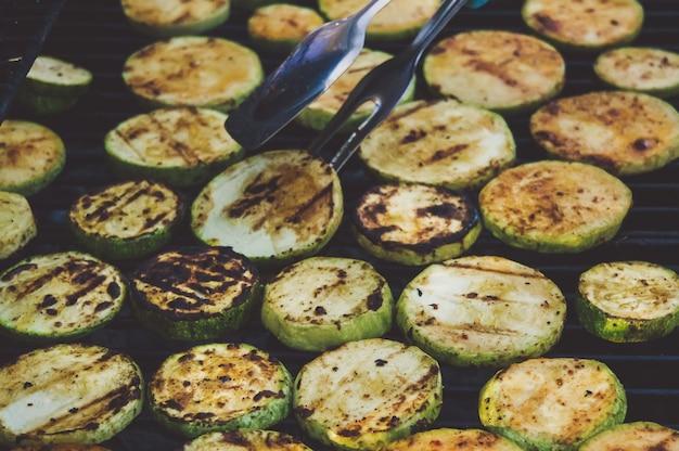 Les mains des cuisiniers retournent des courgettes grillées pinces métalliques sur fond de délicieuses courgettes à la croûte délicieuse.