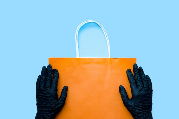 Mains dans un gant chirurgical noir tenant un sac en papier. mesures de précaution à domicile contre le covid-19, sac en papier livré sans contact direct.