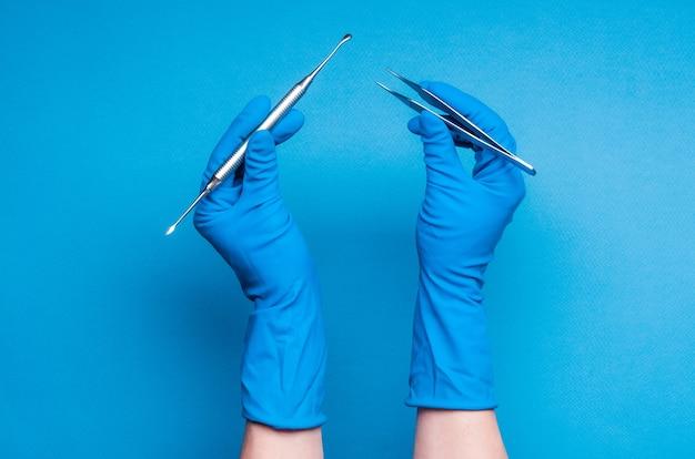 Mains dans des gants bleus tenant des bâtons de chirurgie dentaire sur fond bleu clair