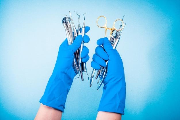 Mains dans des gants bleus tenant du matériel dentaire de chirurgie sur fond bleu clair
