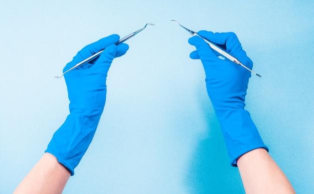 Mains dans des gants bleus tenant des outils dentaires sur fond bleu clair