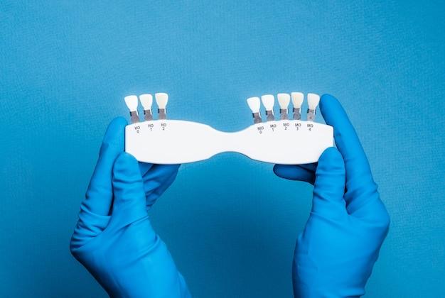 Mains dans des gants bleus tenant une palette de couleurs dentaires sur fond bleu