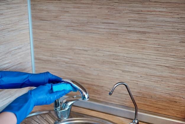 Mains dans des gants de caoutchouc bleu vif
