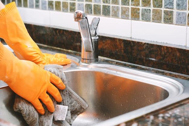 Mains dans des gants en caoutchouc, laver la vaisselle à la cuillère