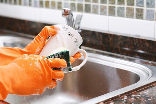 Mains dans des gants en caoutchouc, laver la vaisselle avec du spon