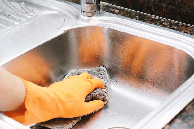 Mains dans des gants de caoutchouc, laver la vaisselle avec spon