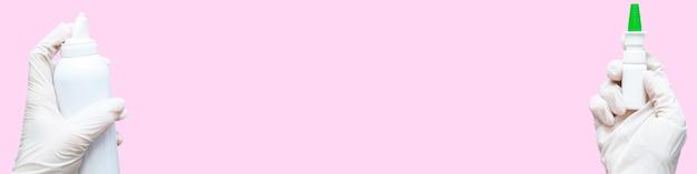 Les mains dans des gants en caoutchouc tiennent un spray et un aérosol ou un antiseptique sur un fond rose, des maquettes, copiez l'espace. bannière