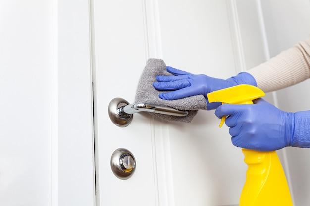 Les mains dans les gants désinfectant la poignée de porte avec un chiffon et un détergent en aérosol
