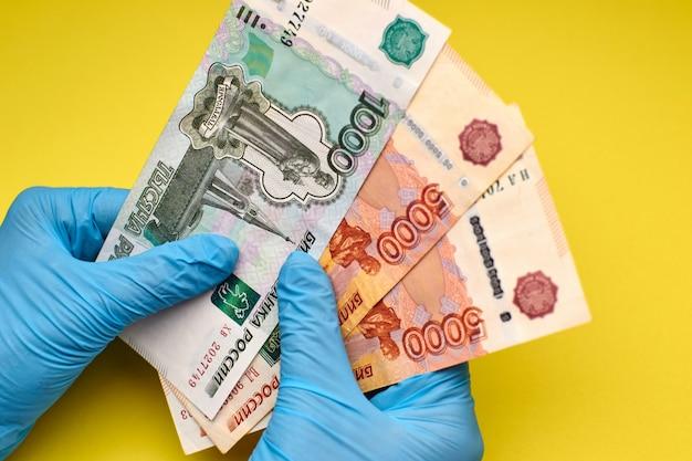 Mains dans des gants détiennent des billets de banque
