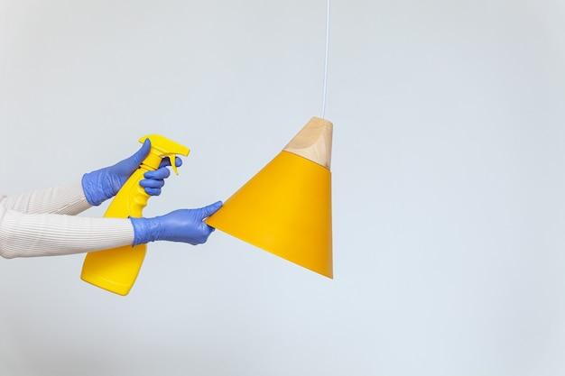 Mains dans les gants enlevant le lustre de lampe électrique de nettoyage de poussière