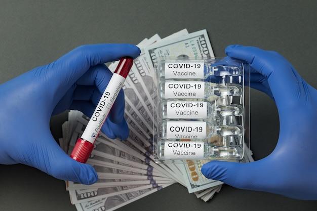 Mains dans des gants en latex contenant le vaccin de covid-19 et tube à essai avec du sang. analyse des prix 2019-ncov