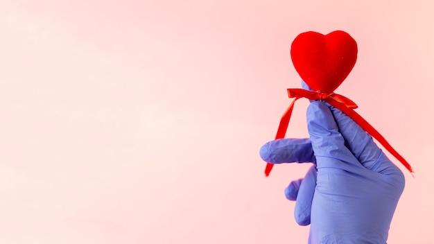 Les mains dans les gants médicaux tiennent le coeur