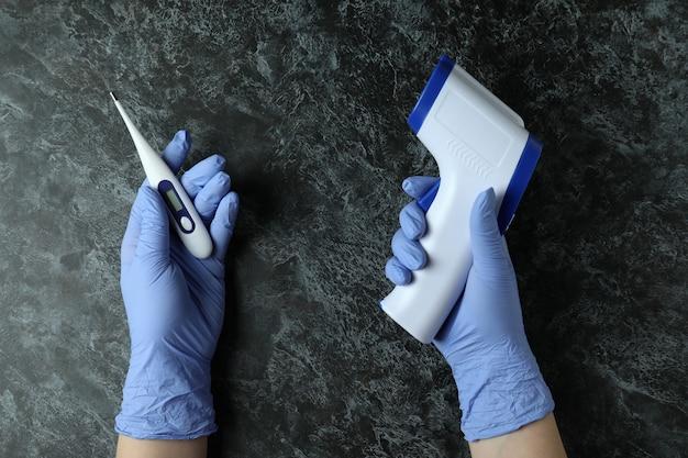 Les mains dans les gants médicaux tiennent des thermomètres numériques sur smokey noir