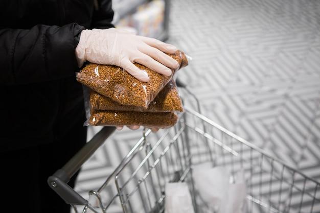 Les mains dans les gants mettent des paquets de sarrasin dans un chariot. sécurité épidémique