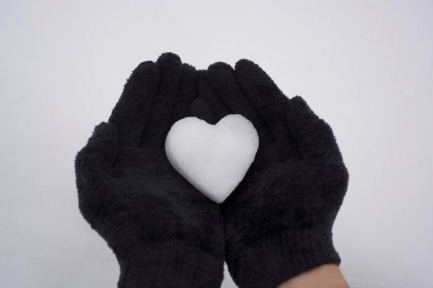 Mains dans des gants noirs tenant le coeur de neige mise au point sélective vue de dessus photo de haute qualité