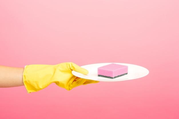 Mains dans des gants de protection jaunes, laver une assiette