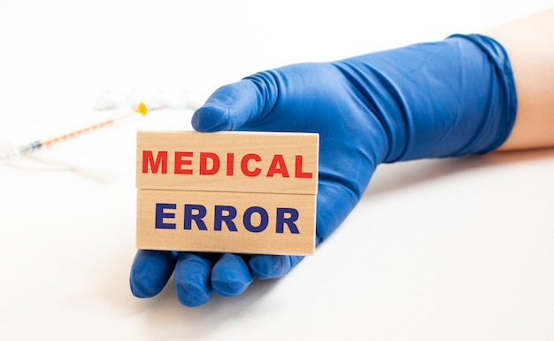 Les mains dans les gants de protection médicale tiennent des cubes en bois avec l'inscription. concept médical.