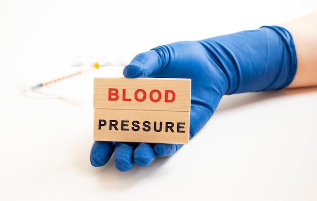 Les mains dans les gants de protection médicale tiennent des cubes en bois avec l'inscription. concept médical
