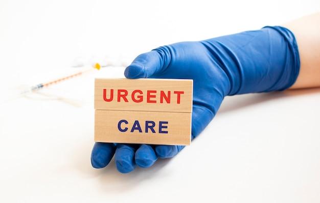 Les mains dans les gants de protection médicale tiennent des cubes en bois avec l'inscription concept médical