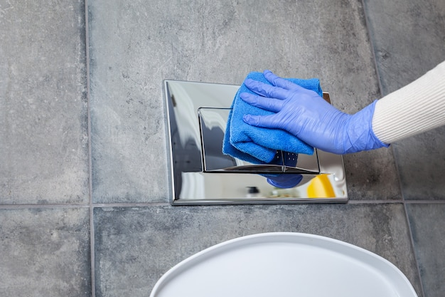 Mains dans des gants de protection nettoyant le bouton de chasse d'eau des toilettes