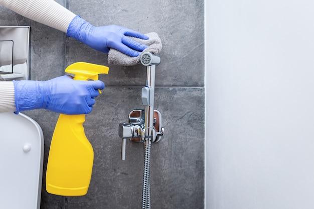 Mains dans des gants de protection nettoyant la douche hygiénique dans la salle sanitaire