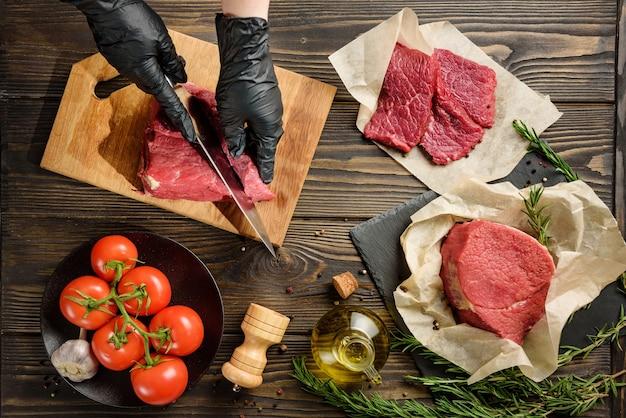 Les mains dans des gants de protection noirs coupent la viande contre la table d'autres produits alimentaires. ingrédients pour la cuisson des steaks.