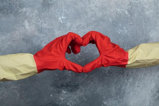 Mains dans des gants de protection rouges donnant le signe du cœur.