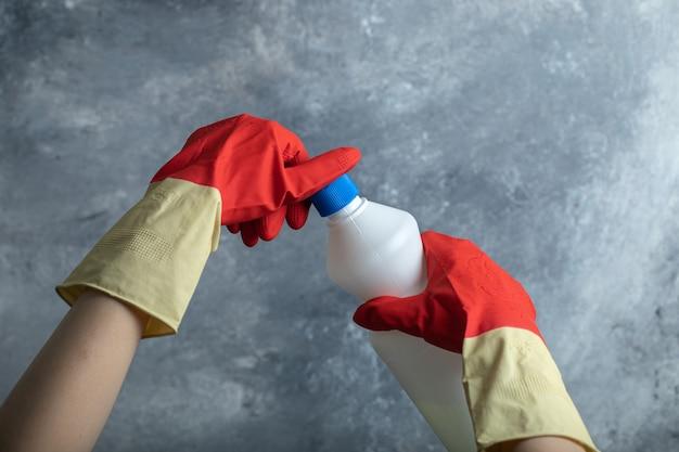 Les mains dans des gants rouges ouvrant le contenant d'eau de javel.