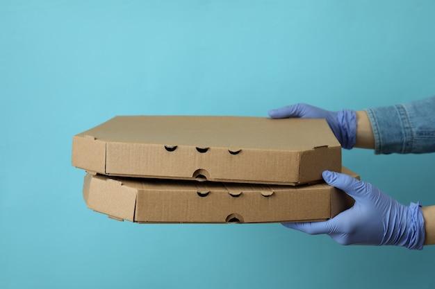 Les mains dans les gants tiennent les boîtes de pizza sur bleu