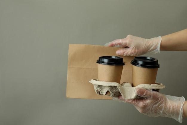 Les mains dans les gants tiennent des gobelets en papier et un sac sur fond gris