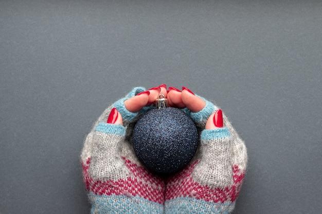 Mains dans des gants tricotés avec boule de noël brillante et avec des ongles scintillants rouges sur fond gris