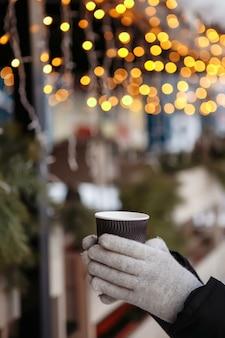 Les mains dans les mitaines tiennent une tasse de café chaud à emporter en hiver