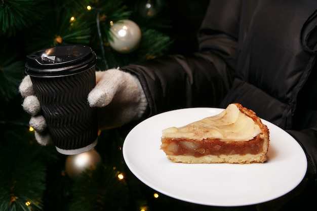 Les mains dans les mitaines tiennent une tasse de café chaud et un morceau de gâteau