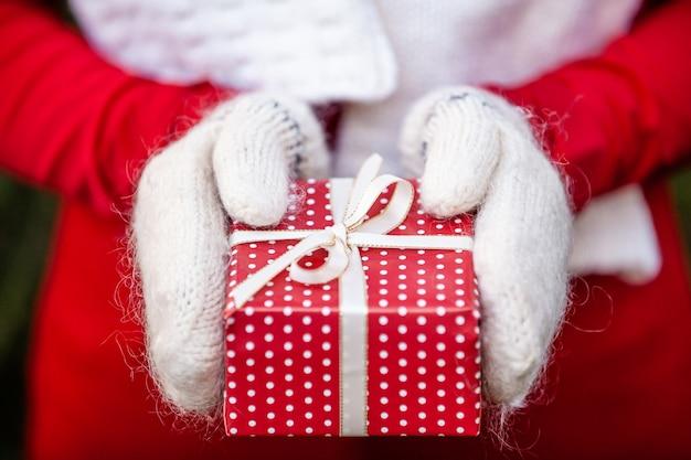 Mains dans les mitaines tricotées tenant une boîte de cadeau de noël à la main
