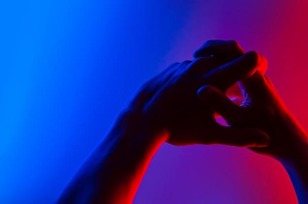 Mains dans le néon coloré contraste bleu rouge.