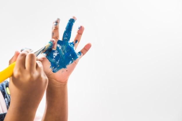 Mains dans la peinture avec une brosse en studio