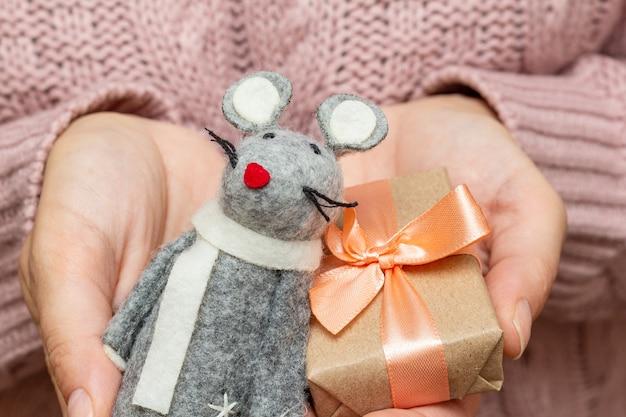Mains dans un pull tricoté tenant un rat et une boîte cadeau. concept de préparation de vacances de noël.