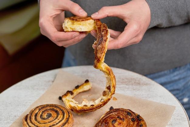 Mains déchirer un morceau de pain avec des graines de pavot sur le fond de la table