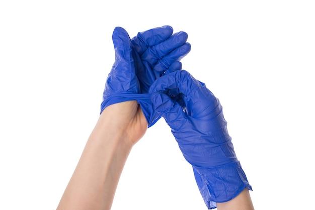 Mains décollant ses gants de protection jetables isolés sur fond blanc
