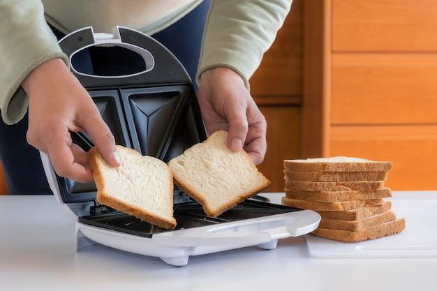 Les mains déposent deux tranches de pain au toster pour les sandwichs
