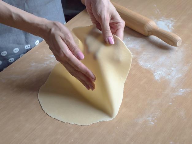 Les mains déroulent la pâte fine.