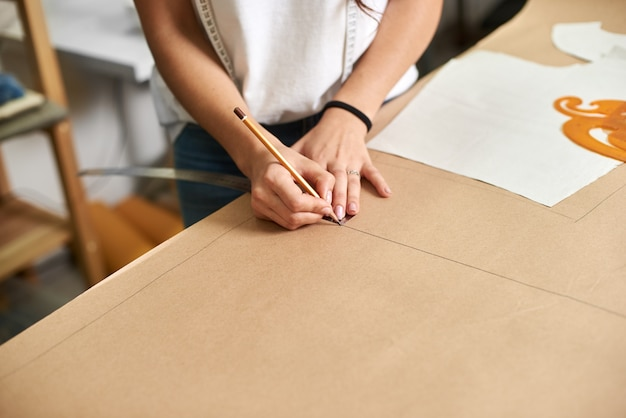 Mains de designer féminines faisant des lignes de dessin sur carton