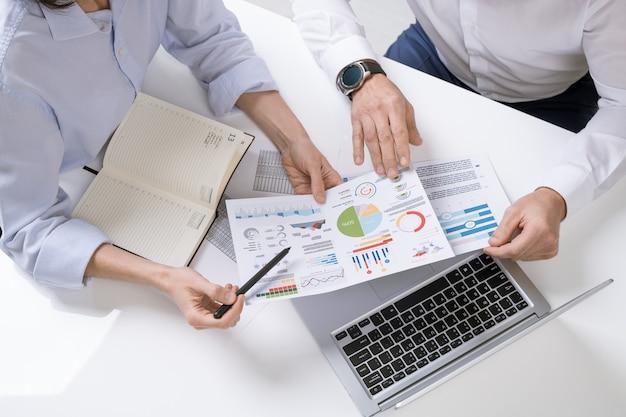 Mains de deux courtiers contemporains discutant des documents financiers avec des graphiques, des tableaux et des diagrammes lors de la réunion